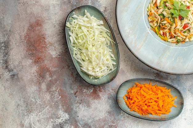 Bovenaanzicht smakelijke groentesalade met gesneden wortel en kool op lichte achtergrond