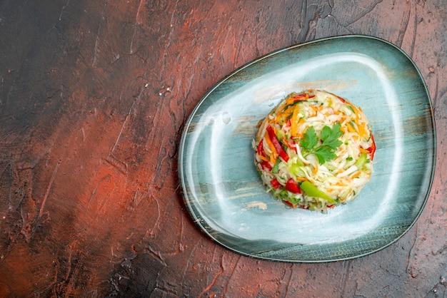 Bovenaanzicht smakelijke groentesalade rond gevormde binnenplaat op de donkere tafel