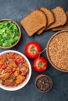 Bovenaanzicht smakelijke groentesoep met greens brood en rauwe boekweit op grijs