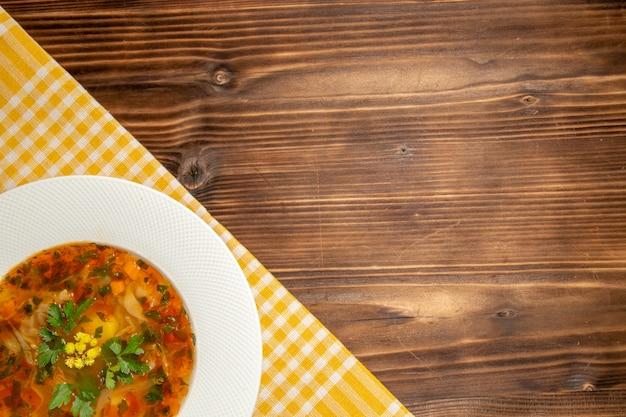 Bovenaanzicht smakelijke groentesoep met greens op het bruine houten bureau soep eten groenten kruiden