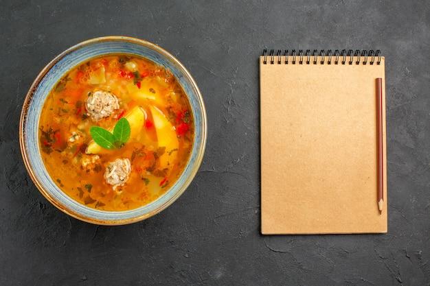 Bovenaanzicht smakelijke groentesoep met vlees en aardappelen op donkere tafel schotel vleesmeel eten