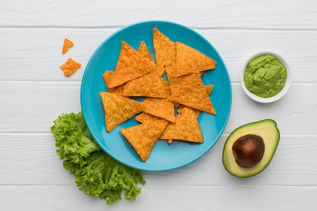 Bovenaanzicht smakelijke guacamole met nacho's klaar om te worden geserveerd