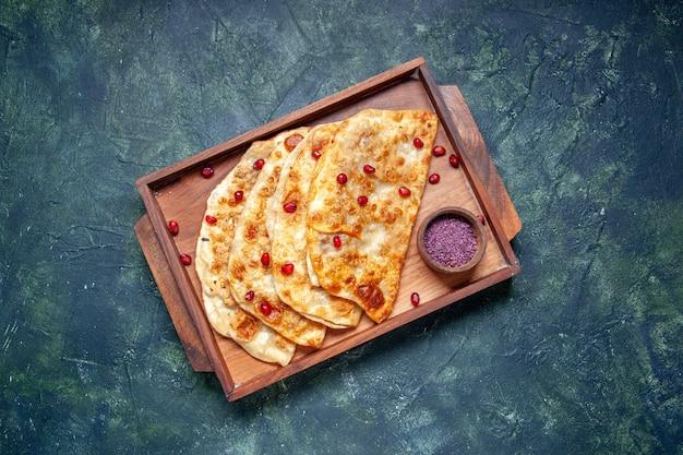 Bovenaanzicht smakelijke gutabs dunne hotcakes met vlees binnen bureau op donkere achtergrond kleur hotcake deeg maaltijd oven taart taart