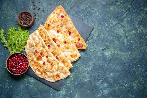 Bovenaanzicht smakelijke gutabs dunne hotcakes met vlees en granaatappels op donkere achtergrond gebak taart taart kleur deeg ovenmaaltijd