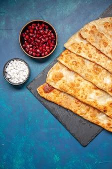 Bovenaanzicht smakelijke gutabs dunne hotcakes met vlees op blauwe achtergrond gebak bak oven taart taart eten maaltijd hotcake kleur