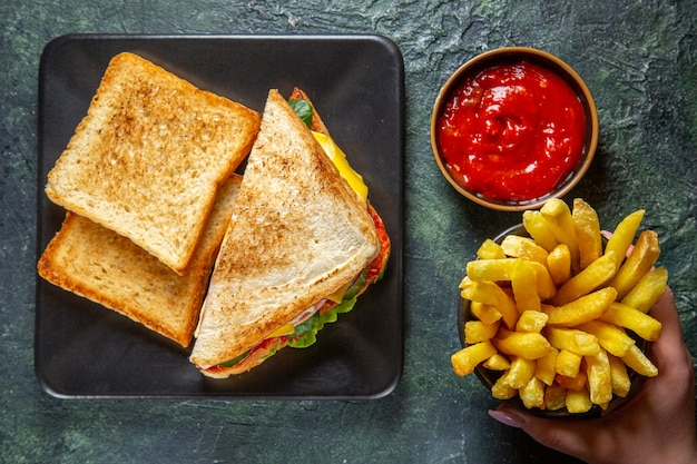 Bovenaanzicht smakelijke ham sandwiches met toast franse frietjes en tomatenpuree op donkere ondergrond