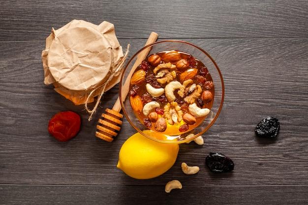 Bovenaanzicht smakelijke honing met noten en citroen