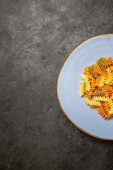 Bovenaanzicht smakelijke italiaanse pasta ongebruikelijke gekookte spiraalvormige pasta in het donker