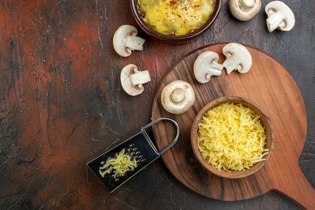 Bovenaanzicht smakelijke julienne in kom rauwe champignons rasp geraspte mosarella in kom op snijplank op bruine tafel