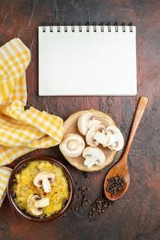 Bovenaanzicht smakelijke julienne in kom zwarte peper in houten lepel champignons op houten bord notitieblok op donkerrode tafel