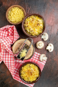 Bovenaanzicht smakelijke julienne in kom zwarte peper in houten lepel champignonsrasp op houten bord op donkerrode tafel