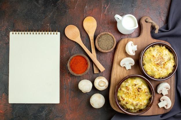 Bovenaanzicht smakelijke julienne in kommen op snijplank houten lepels kruiden in kleine kommen champignons notitieboekje op bruin