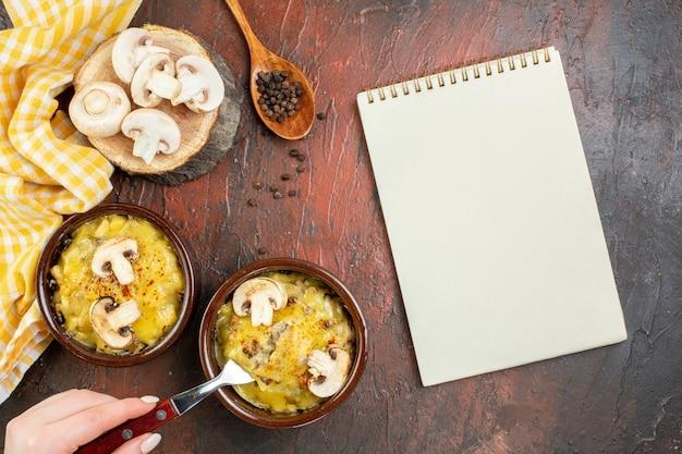 Bovenaanzicht smakelijke julienne in kommen vork in vrouwelijke hand notitieblok houten lepel op donkerrode tafel