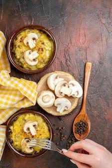 Bovenaanzicht smakelijke julienne in kommen vork in vrouwelijke hand zwarte peper in houten lepel champignons op houten bord op donkerrood