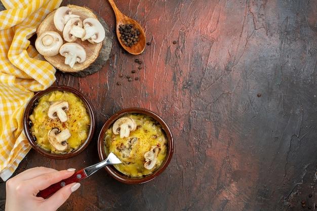 Bovenaanzicht smakelijke julienne in kommen vork in vrouwelijke hand zwarte peper in houten lepel op donkerrode tafel