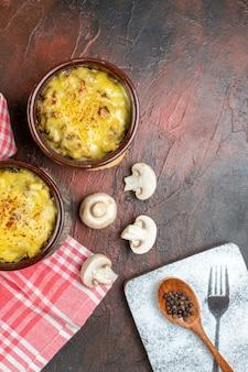 Bovenaanzicht smakelijke julienne in kommen zwarte peper in houten lepel champignons op donkerrode tafel