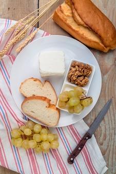 Bovenaanzicht smakelijke kaas met druiven en walnoten op een plaat