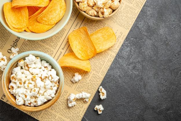 Bovenaanzicht smakelijke kaaschips met verschillende snacks voor filmtijd op de donkere achtergrond