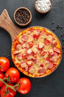 Bovenaanzicht smakelijke kaaspizza met worstjes en tomaten op donkere tafel