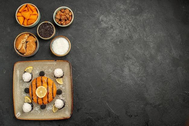 Bovenaanzicht smakelijke kleine taart met kokos snoepjes op donkere oppervlakte taart cookie dessert cake biscuit thee snoep