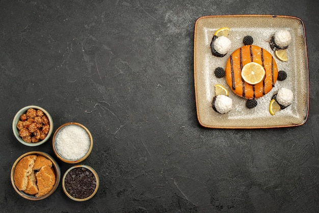 Bovenaanzicht smakelijke kleine taart met kokossnoepjes op donkere oppervlakte dessert cake biscuit thee snoep