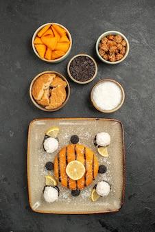 Bovenaanzicht smakelijke kleine taart met kokossnoepjes op donkere oppervlakte taart dessert cake biscuit thee snoep koekje