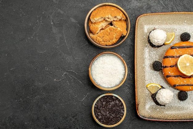 Bovenaanzicht smakelijke kleine taart met kokossnoepjes op donkere oppervlakte taart dessert cake biscuit thee snoep