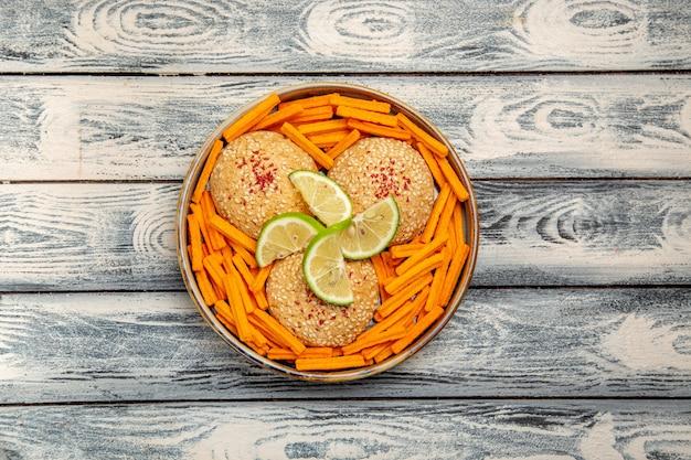 Bovenaanzicht smakelijke koekjes met plakjes citroen en beschuit op een grijs bureau koekje suikertaart taart zoet koekje