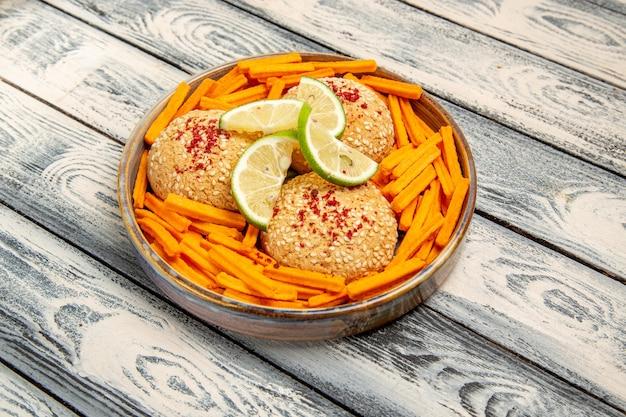 Bovenaanzicht smakelijke koekjes met plakjes citroen en beschuit op rustiek grijs bureaukoekje suikertaart taartkoekje