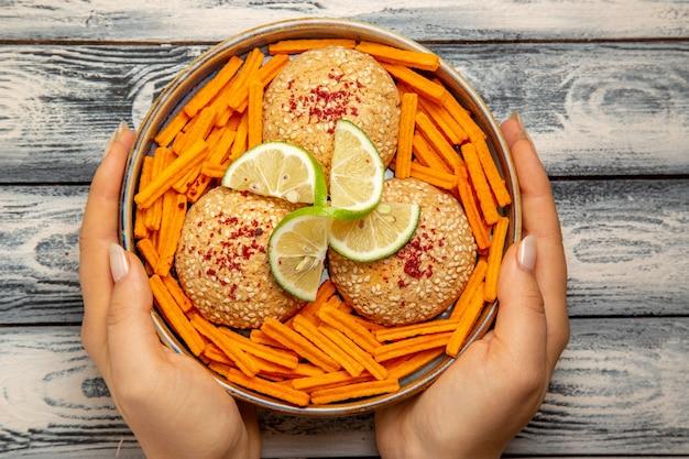 Bovenaanzicht smakelijke koekjes met schijfjes citroen en beschuit op het rustieke grijze bureau koekje suikertaart snack zoet koekje