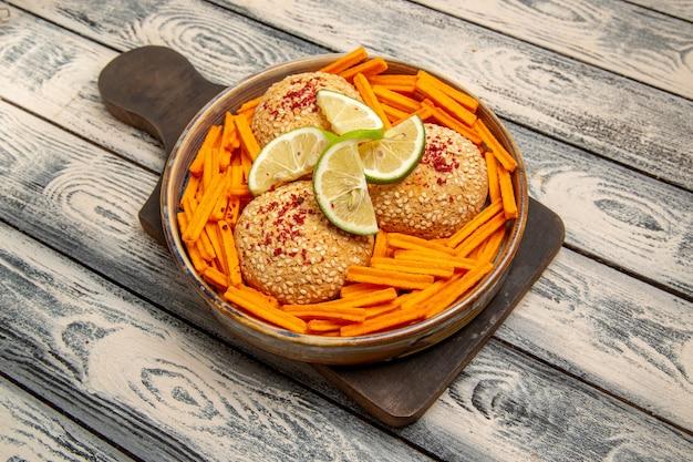 Bovenaanzicht smakelijke koekjes met schijfjes citroen en beschuit op het rustieke grijze bureau snack koekje suiker zoete cake cookie