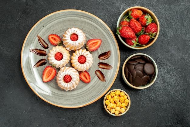 Bovenaanzicht smakelijke koekjes met snoep kommen van hazelnoten aardbei en chocolade naast koekjes met chocolade en aardbei op donkere tafel