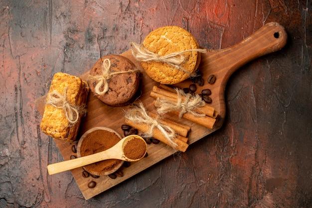 Bovenaanzicht smakelijke koekjes vastgebonden met touw cacao in kom koffiebonen in kom kaneel op houten bord op donkere tafel
