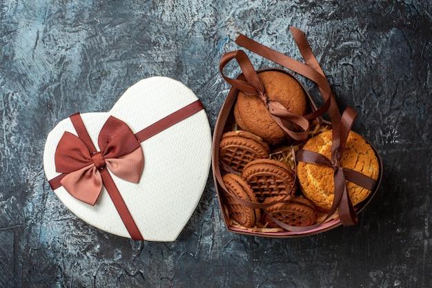 Bovenaanzicht smakelijke koekjes vastgebonden met touw in hartvormige doos en deksel op grijze tafel
