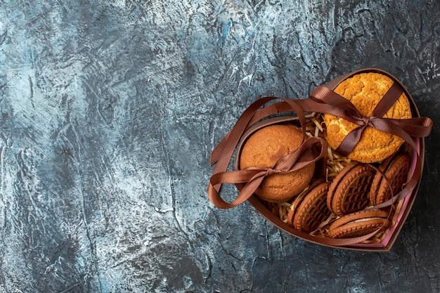 Bovenaanzicht smakelijke koekjes vastgebonden met touw in hartvormige doos op donkere achtergrond