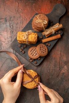 Bovenaanzicht smakelijke koekjes vastgebonden met touw, kaneelstokjes, koekjes op houten serveerplankkoekjes in vrouwelijke handen op donkere tafel