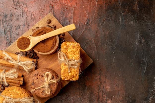Bovenaanzicht smakelijke koekjes vastgebonden met touw koffiebonen in kom kaneel op houten bord op donkere tafel