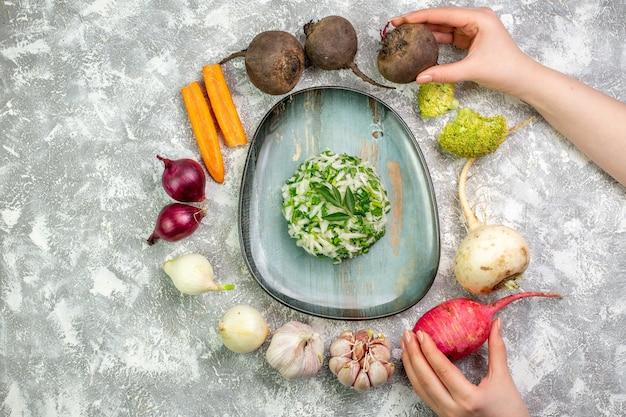 Bovenaanzicht smakelijke koolsalade met verse groenten op witte tafel