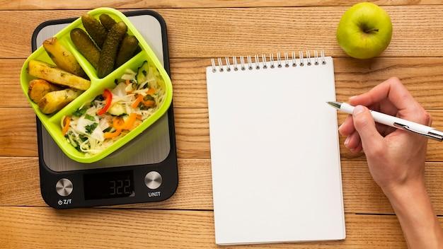 Bovenaanzicht smakelijke maaltijdregeling met leeg notitieboekje