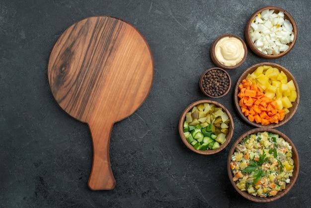 Bovenaanzicht smakelijke mayyonaise salade met gesneden verse groenten op zwart