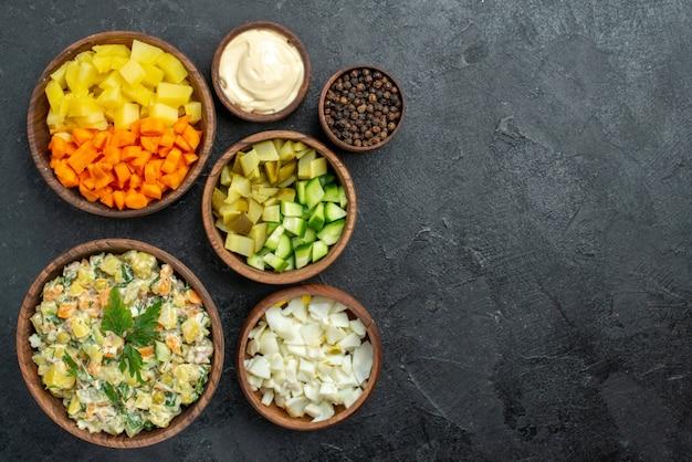 Bovenaanzicht smakelijke mayyonaise salade met vers gesneden groenten op grijs