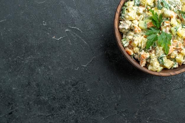 Bovenaanzicht smakelijke mayyonaisesalade binnen bruine plaat op grijs