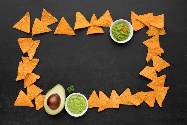 Bovenaanzicht smakelijke nacho's met guacamole op tafel