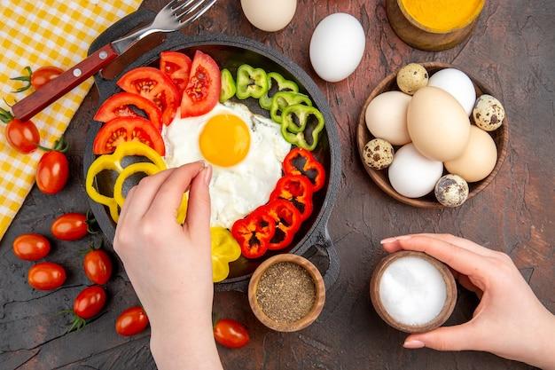 Bovenaanzicht smakelijke omelet met gesneden paprika en smaakmakers op de donkere tafel