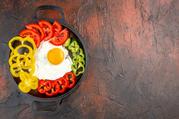 Bovenaanzicht smakelijke omelet met gesneden paprika en tomaten op donkere tafel