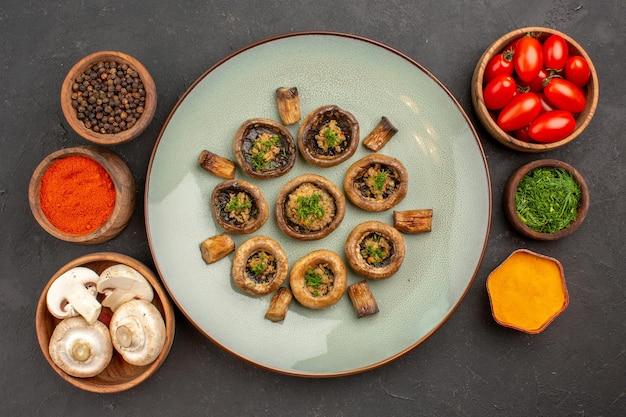 Bovenaanzicht smakelijke paddenstoelenschotel met tomaten en kruiden op donkere oppervlakteschotel dinermaaltijd kokende paddestoel