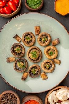 Bovenaanzicht smakelijke paddenstoelenschotel met tomaten en smaakmakers op donkere oppervlakteschotel maaltijd koken paddestoeldiner