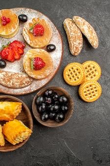 Bovenaanzicht smakelijke pannenkoeken met verschillende zoetigheden op het donkere oppervlak suikertaart dessert