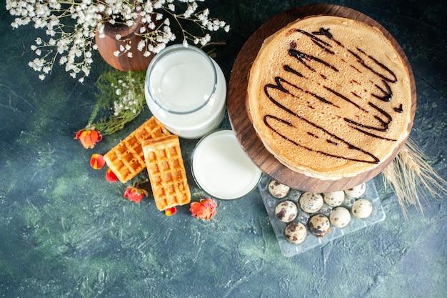 Bovenaanzicht smakelijke pannenkoeken met verse melk en noten op donkerblauwe achtergrond cake melk dessert honing ontbijt ochtend zoete taart