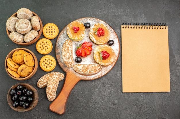 Bovenaanzicht smakelijke pannenkoeken met zoete taarten en fruit op donker bureau
